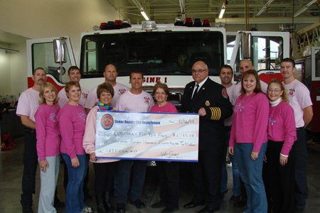 Cedar Rapids firefighters wore pink T-shirts in October 2013 to support breast cancer awareness. They also contributed $2,785.08 of the proceeds from the sales of the pink T-shirts to the EFY Fund.